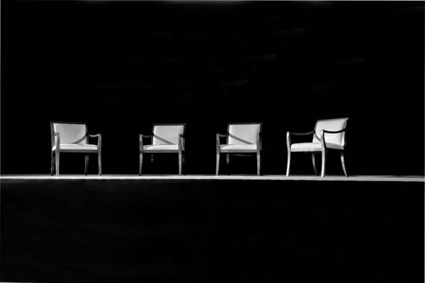 Four empty chairs on a stage